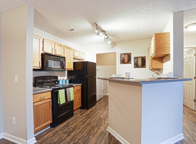 kitchen with ample cabinetry, efficient black appliances, and track lighting at The Point at Fairview Apartments, Prattville, AL