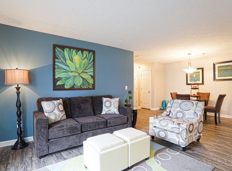living room with accent wall, hardwood-style floors, and model furnishings at The Point at Fairview Apartments, Alabama