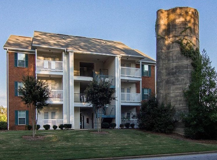Exterior of apartment building with private patios and historic silo at The Point at Fairview Apartments, Prattville, AL