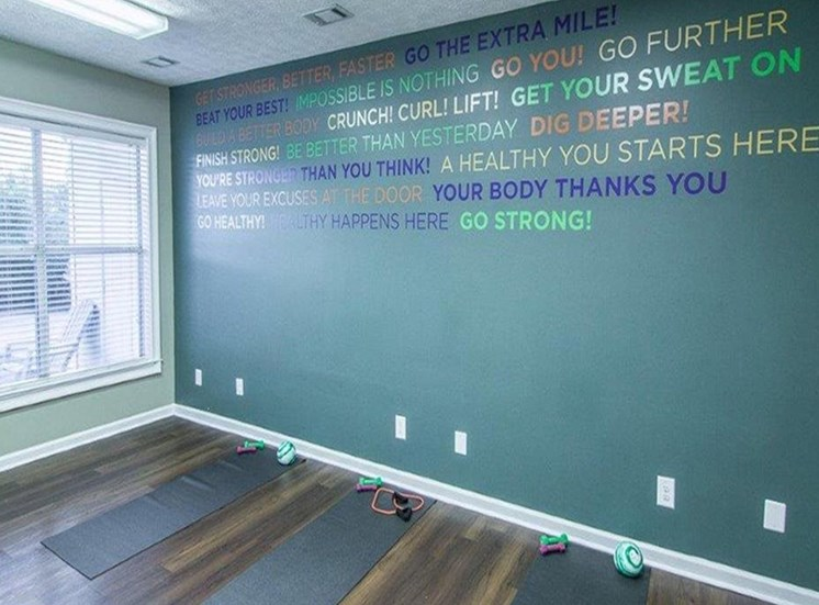 fitness center with large window, yoga mats, and motivational quote on wall at The Point at Fairview Apartments, Prattville, AL, 36066