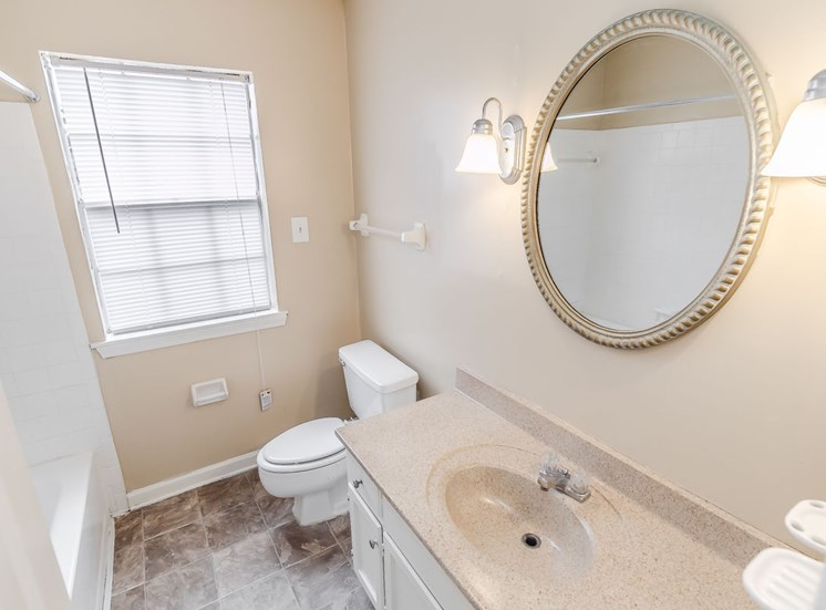bathroom with large vanity, window, and sconce lighting at Hampton House Apartments, Jackson, MS, 39211