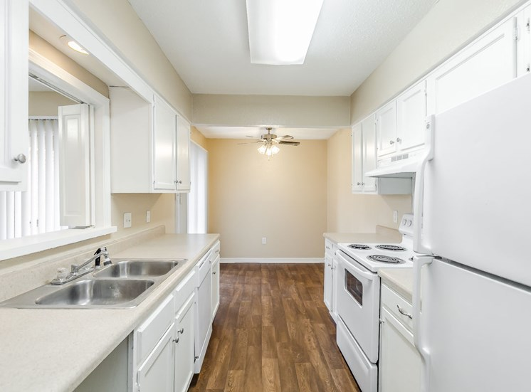 Kitchen with white cabinets and appliances and wood style floors at Hampton House Apartments, Jackson, Mississippi