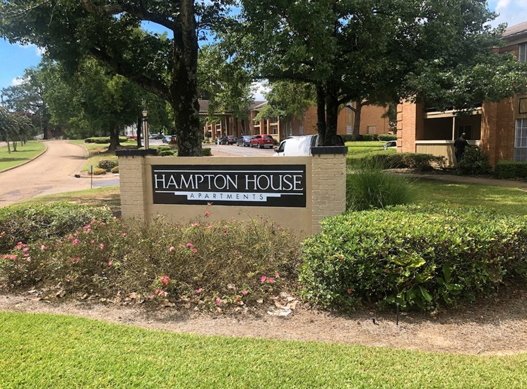 Monument Sign in front of Hampton House Apartments with lush landscaping