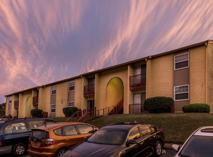 sunset over building and parking lot with cars at Reserve at Midtown Apartments, Tallahassee, 32303