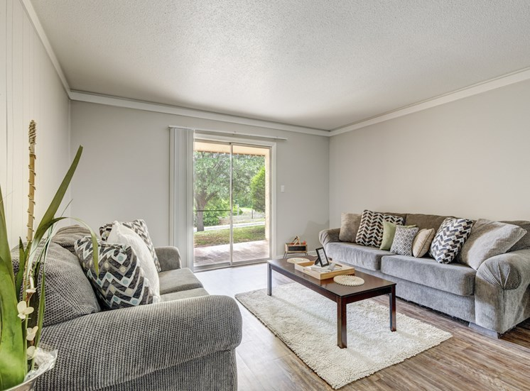 spacious living room with plank-style flooring and large sliding glass doors at Reserve at Midtown Apartments, Tallahassee, Florida