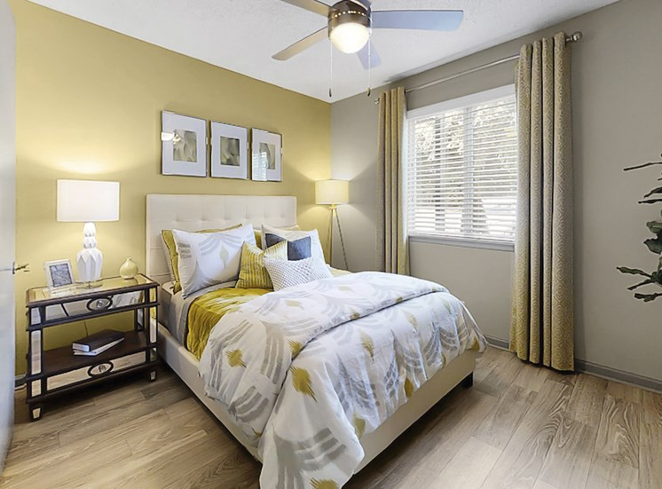 bedroom with ceiling fan, large window, and plank-style flooring