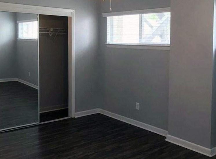 Bedroom with hardwood-style floor and mirrored closet door