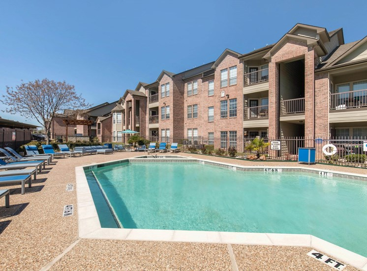 Swimming Pool and tanning deck with apartment exterior in the background