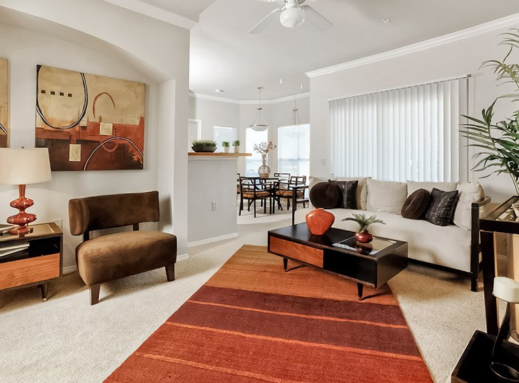 Living room with sofa, coffee table and dining room in the background
