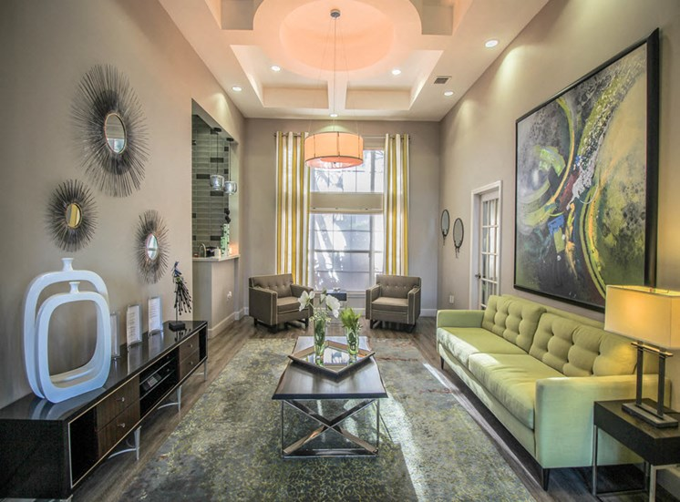Clubhouse seating area with couch, two chairs, tree tables, a lamp, table and wall decor