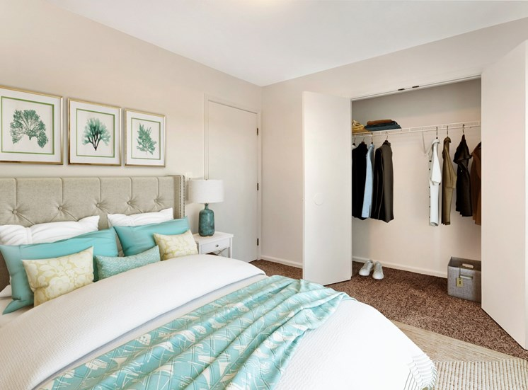 Bedroom with queen size bed, with night stand with lamp. Closet with clothes hanging from the wire shelves