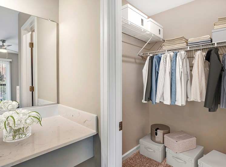A virtually staged walk-in closet with gray walls and white trim. The closet is staged with a variety of clothing, white boxes, and linens. A marble countertop vanity area with mounted mirror is located just outside of the closet.