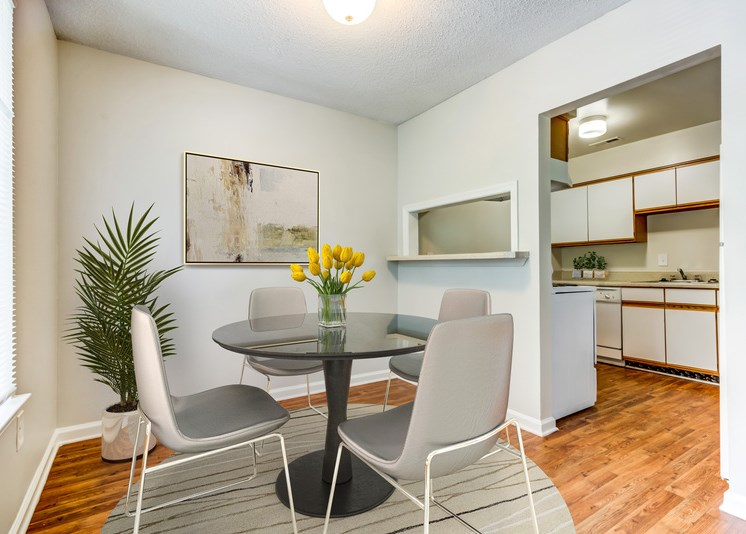 A virtually staged dining room with hardwood style flooring, white walls, a single window with blinds, and direct access to the kitchen in the background. It is staged with a glass top round dining table with four gray chairs, a circular gray area rug under the table, framed artwork on the wall, a large green plant and a vase of yellow flowers positioned on the table.