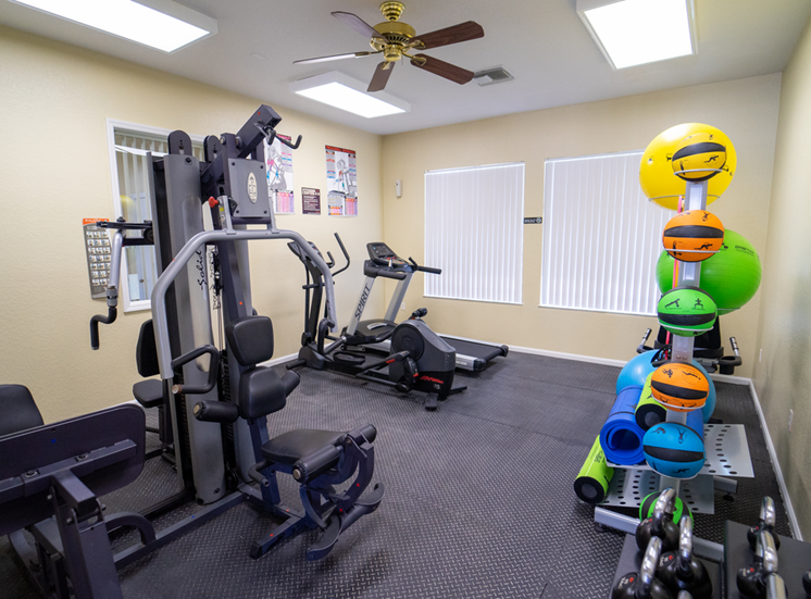 Fitness center equipped with strength training equipment, cardio equipment, and yoga equipment