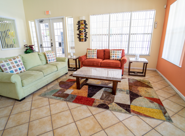 Clubhouse lounge with couches, coffee table, floor rug, tiled floors, side tables, and large windows for natural lighting