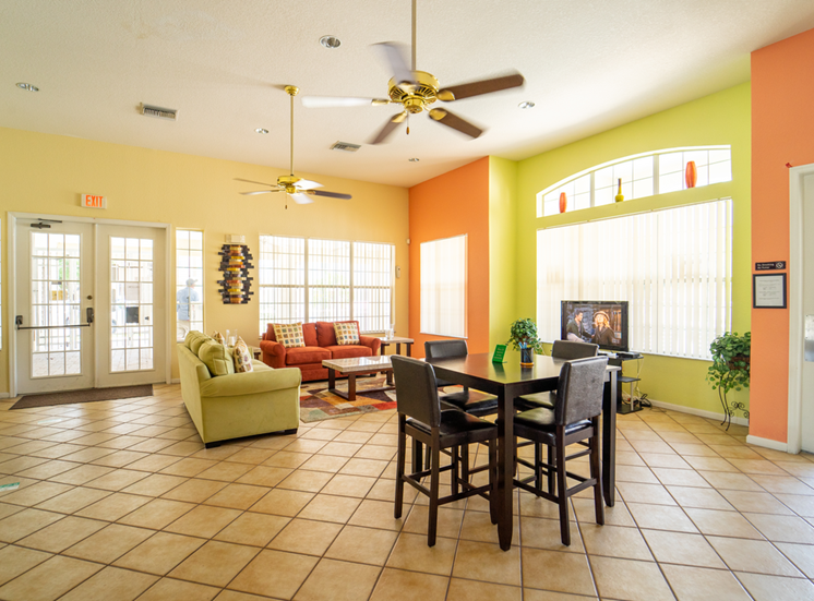Clubhouse lounge with couches, chairs, coffee table, tiled flooring, and multi speed ceiling fan