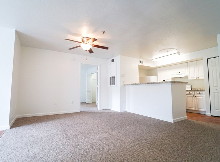 Spacious living room with carpet flooring and multi speed ceiling fan