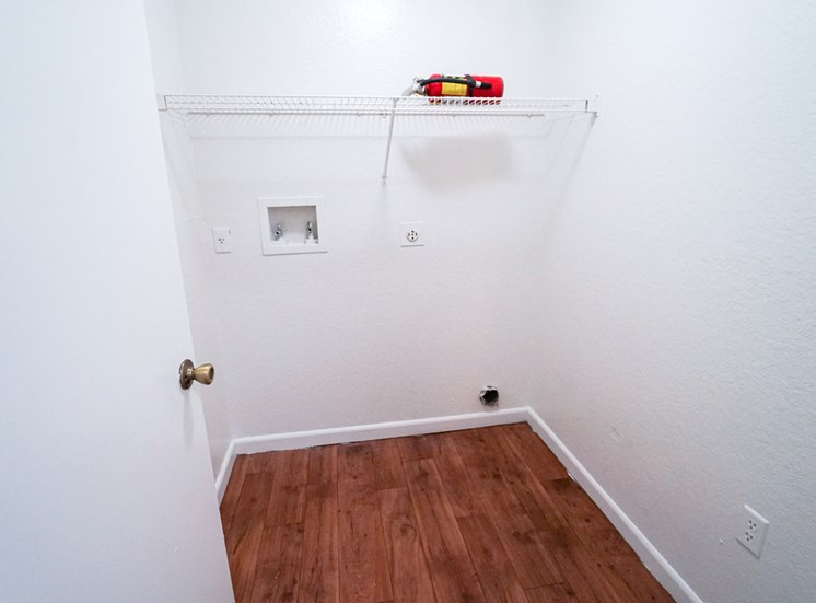 Full-sized washer and dryer room with hardwood style flooring