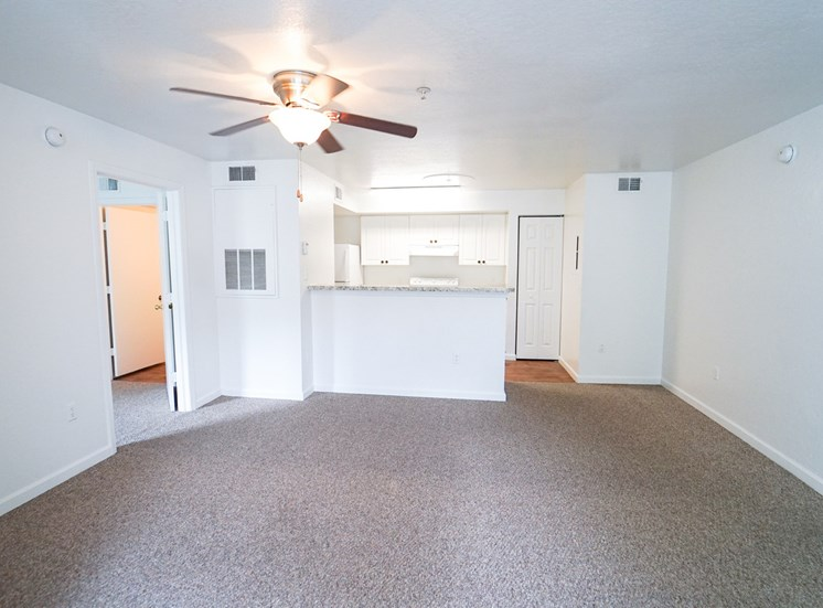 Living room with carpet flooring, multi speed ceiling fan, and kitchen breakfast bar