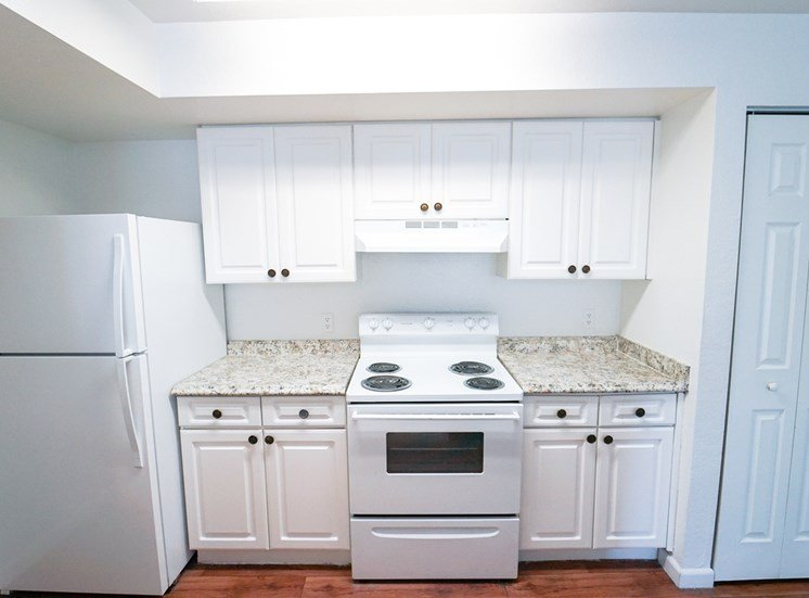 Kitchen with hardwood style flooring, white cabinetry and white appliances