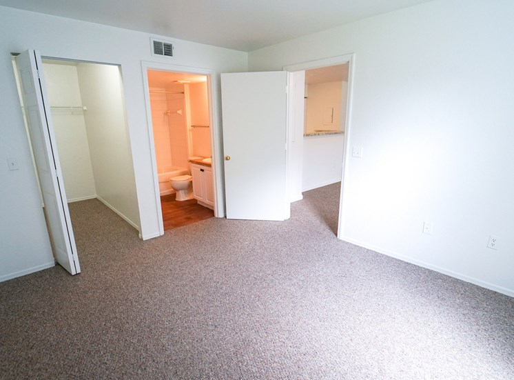 Bedroom with carpet flooring, large walk-in closet, and in-suite bathroom