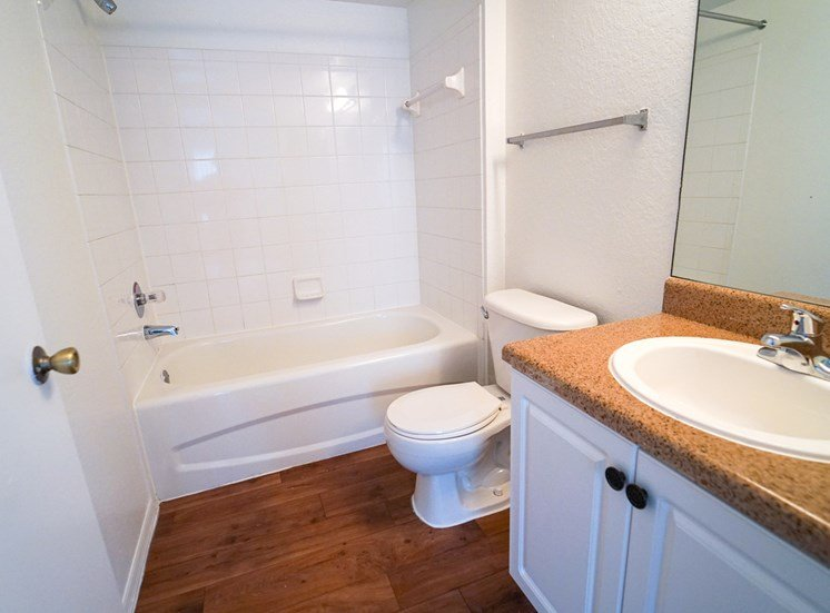 Bathroom with hardwood style flooring, tiled shower, large mirror and vanity lighting