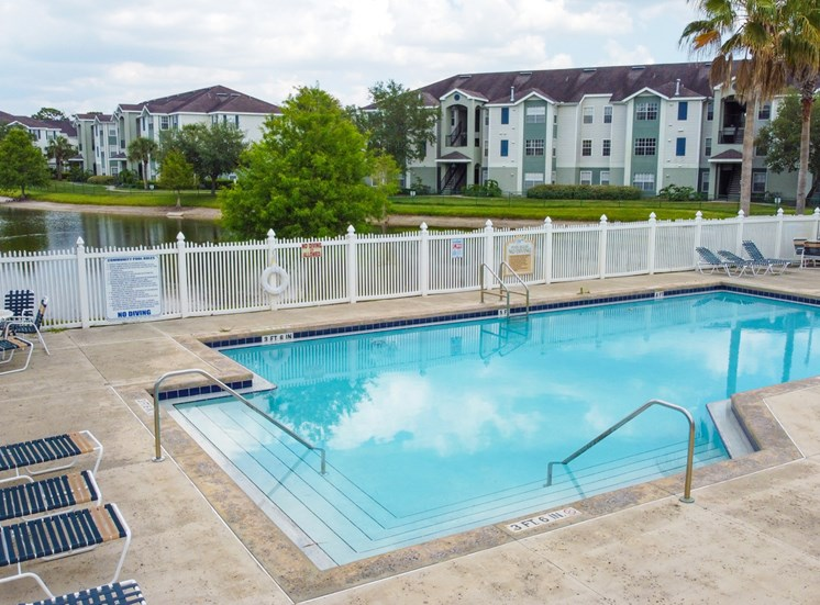 Community pool with sundeck, lounge chairs, with lake view surrounded by white metal fence with palm trees and building exteriors and lake in the background