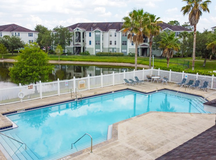 Community pool with sundeck, lounge chairs, with lake view surrounded by white metal fence with palm trees and building exteriors in the background