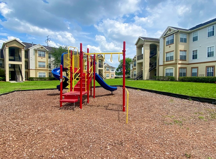 Yellow and Red Playground set with two blue slides in a bed of mulch with buildings and tree in the background