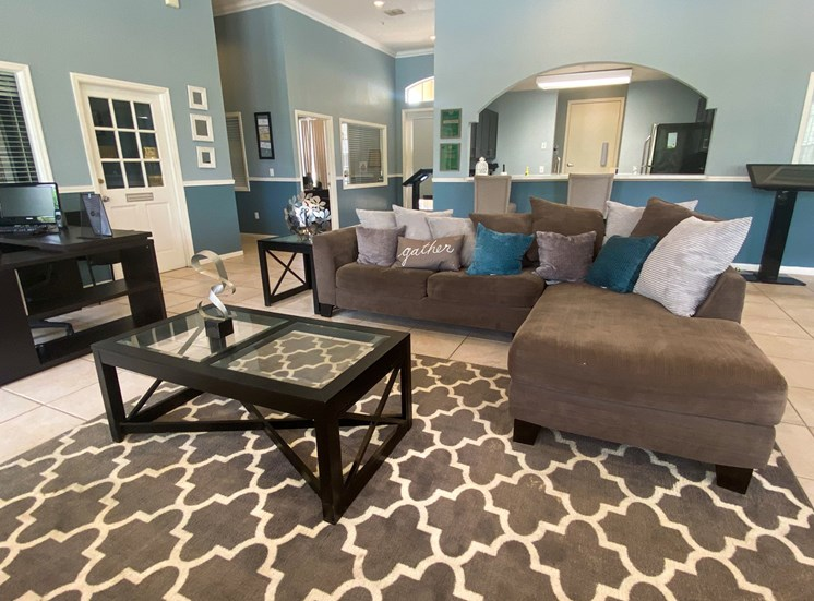 Clubhouse Interior with sectional couch, coffee table, leasing desk and kitchen in the back ground