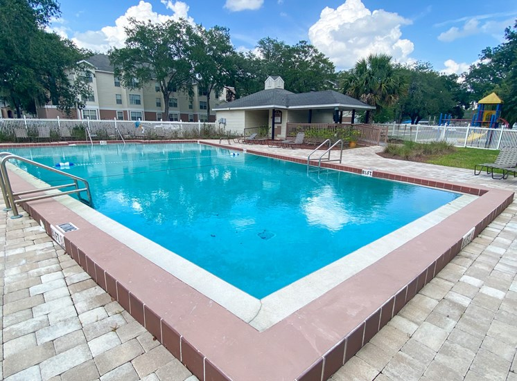 Community pool with pavers and sundeck, lounge chairs, surrounded by white fence with trees, playground, and building exteriors in the background