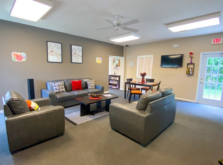 Interior of the clubhouse with carpeted flooring, couches, coffee table, and ceiling fan, mounted tv, dining table, and fitness center in the background