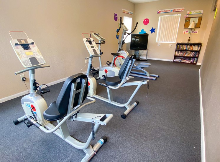 Fitness center with two exercise bikes, elliptical, tv, and bookcase on the back ground
