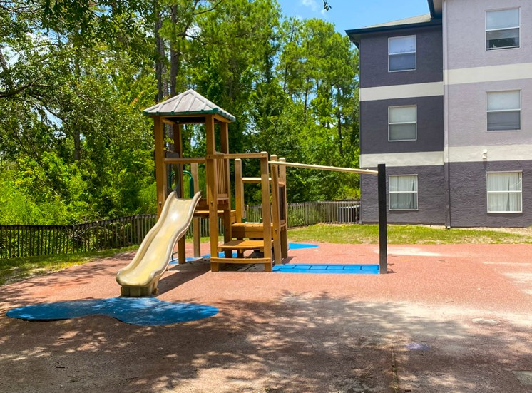 Outdoor playground with slide, latter, surrounded by landscaping and apartment building exterior in the background