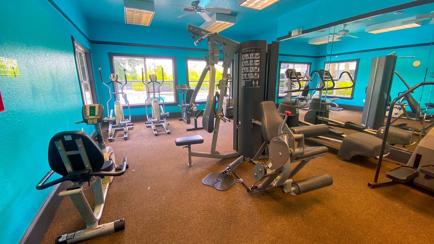Fitness center with cardio equipment, strength training equipment, and large windows for natural lighting