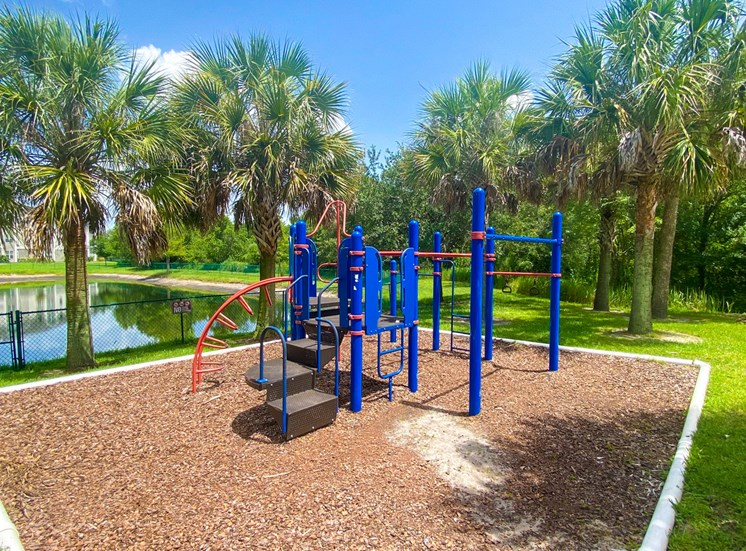Blue and red playground with jungle gym in a bed of mulch with building exteriors, trees, and enclosed lake by green fence in the background
