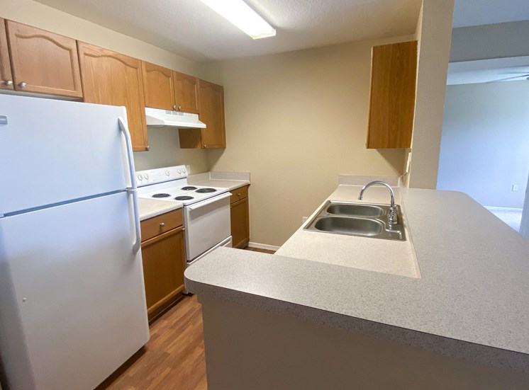 Kitchen with hardwood style flooring, white appliances, double basin sink, and breakfast bar