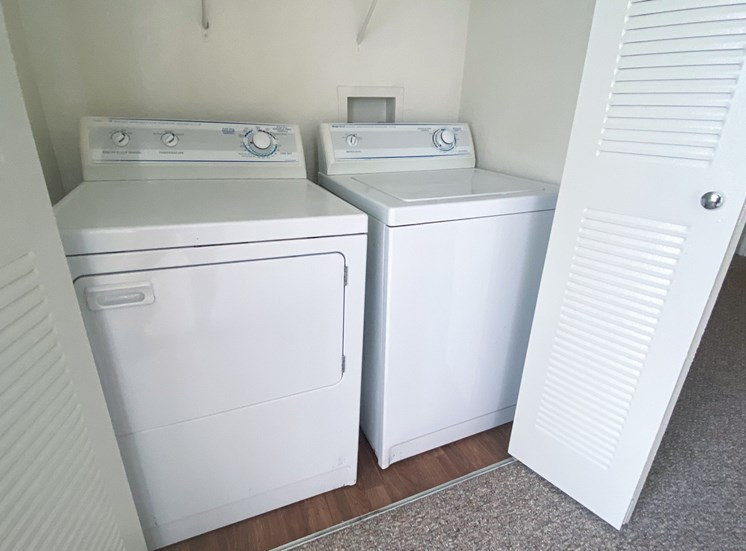 Full sized washer and dryer connections with storage wrack, and hardwood style flooring