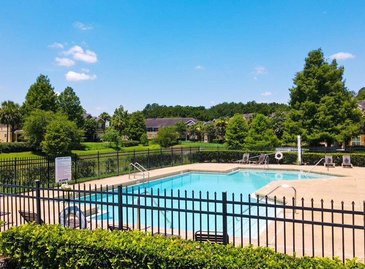 Community pool with sundeck, lounge chairs, surrounded by black metal fence with trees, lake, and building exteriors in the background