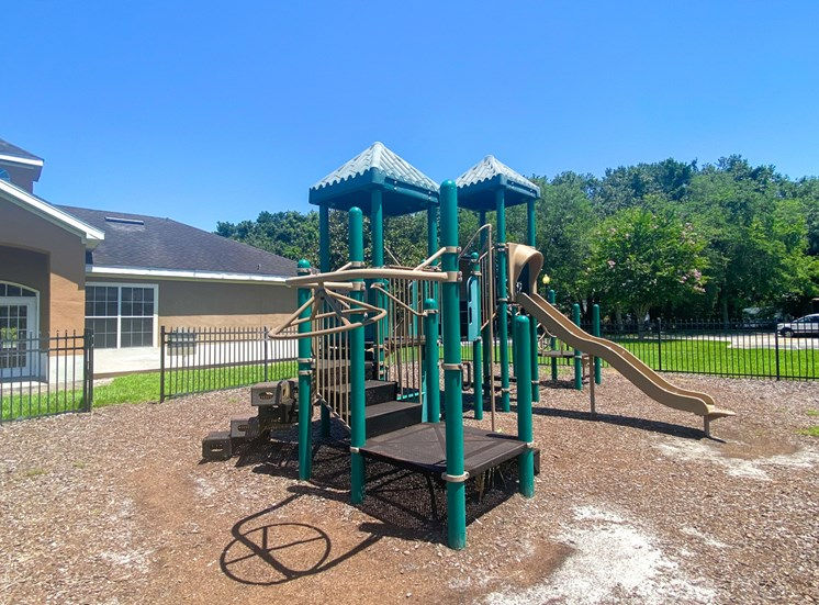 Green and yellow playground with jungle gym and slide in a bed of mulch surrounded by black metal fence with building exteriors and trees in the background