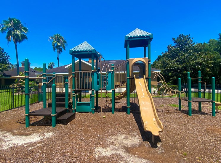 Green and yellow playground with jungle gym and slide in a bed of mulch surrounded by black metal fence with building exteriors in the background
