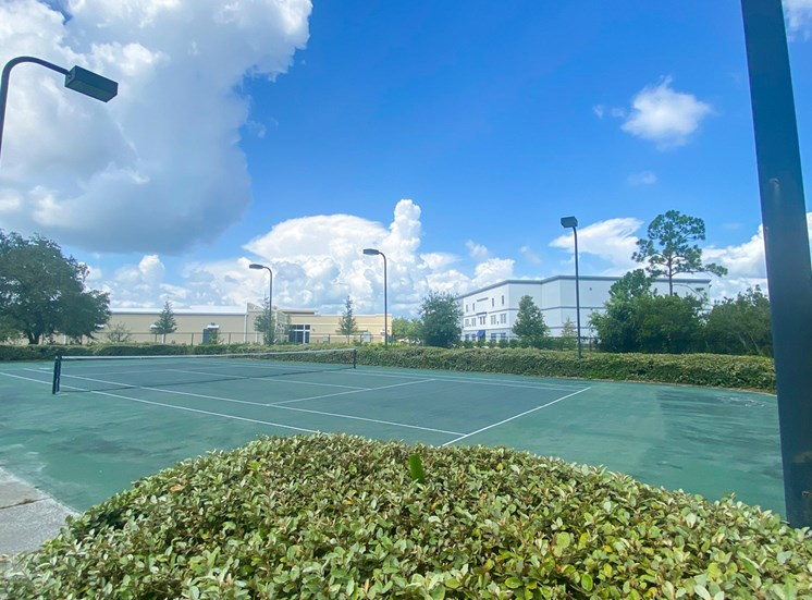 Outdoor tennis court with apartment building exterior in the background