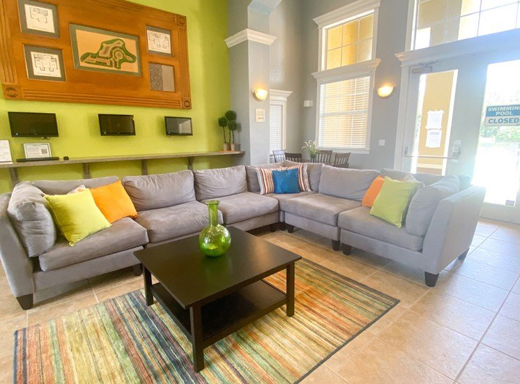 Clubhouse lounge with couch, coffee table, tiled flooring, and floor rug