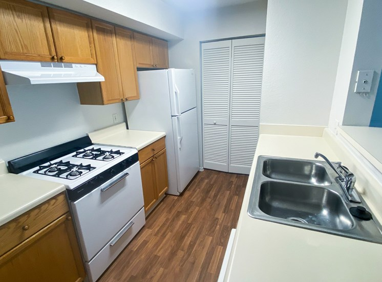 Kitchen featuring brown wood cabinets, white appliances, white countertop, breakfast bar overlooking living room gas stove, and door leading to laundry room in the background