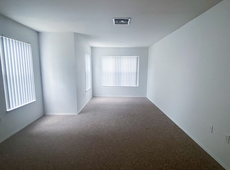 Carpeted Living Room with three windows