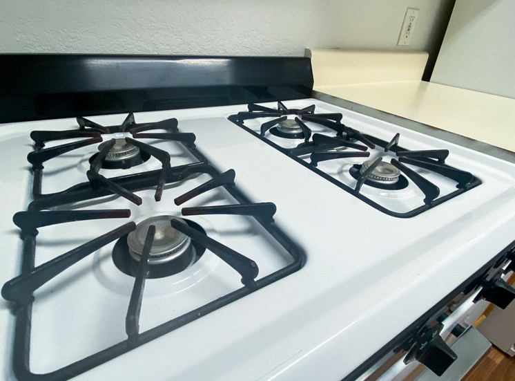 White and black gas stove by white kitchen countertops