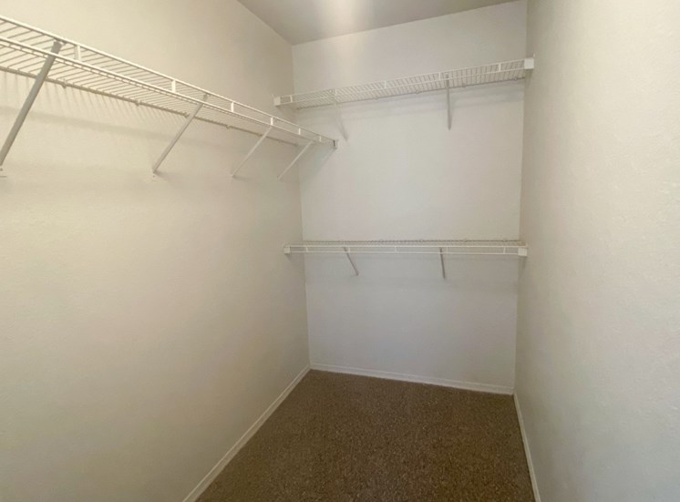 Spacious carpeted closet with mounted metal shelves