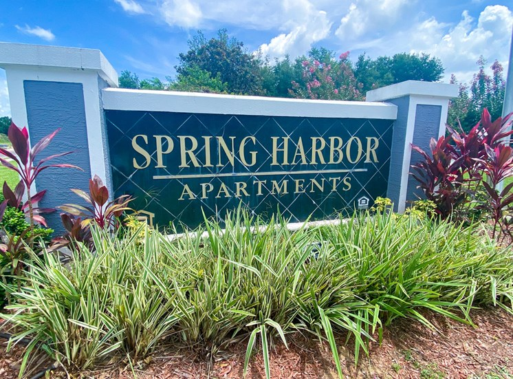 Property Sign with landscaping shrubbery underneath it and trees in the back ground
