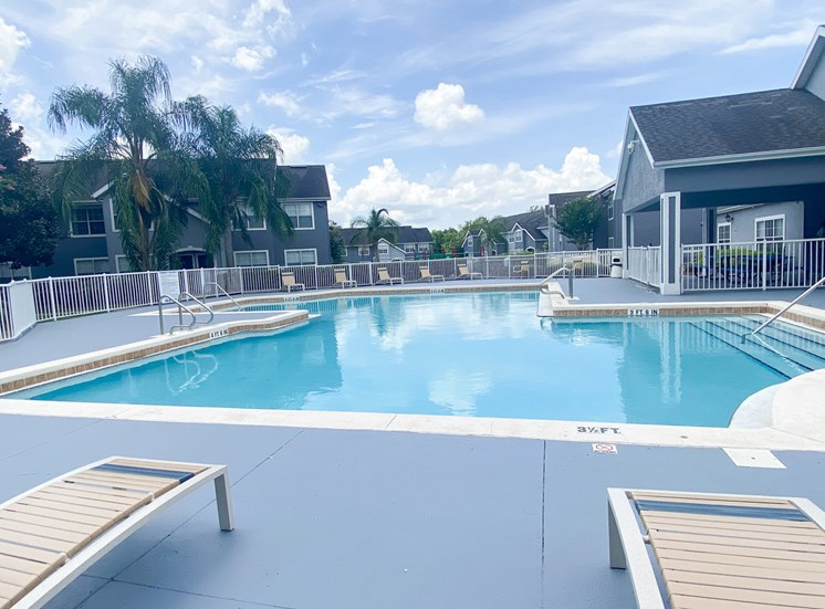 Community pool with sundeck, lounge chairs, with lake view surrounded by white metal fence with palm trees and building exteriors, palm trees, and trees in the background