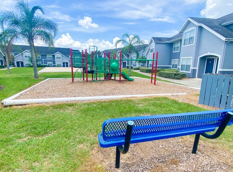 Green and Red Playground set in a bed of mulch with buildings and palm tree in the background, and a  blue bench in the front